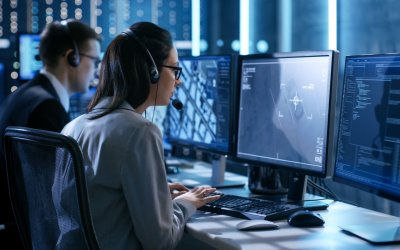 Female working in a Surveillance Team Gives Instructions with the Help of the Headsets. In the Background People Working and Monitors Show Various Information.